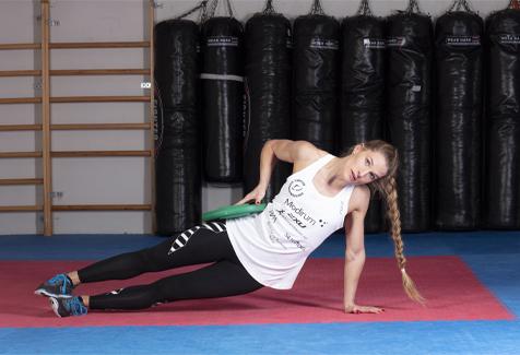 Thea Næss sideplakeøvelse  med vektskive hofte ned i gulv