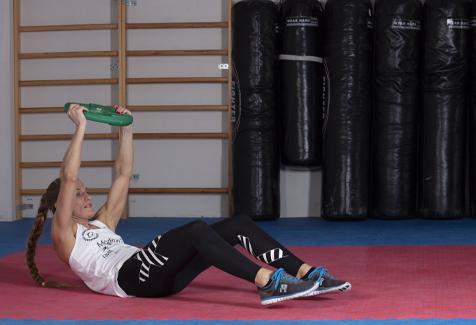 Thea Næss på rygg med vektskive situps øvelse