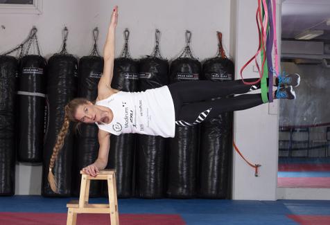 Thea Næss med armer på benk og bena i treningsstrikk